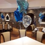 blue foil star helium balloon bunches on tables