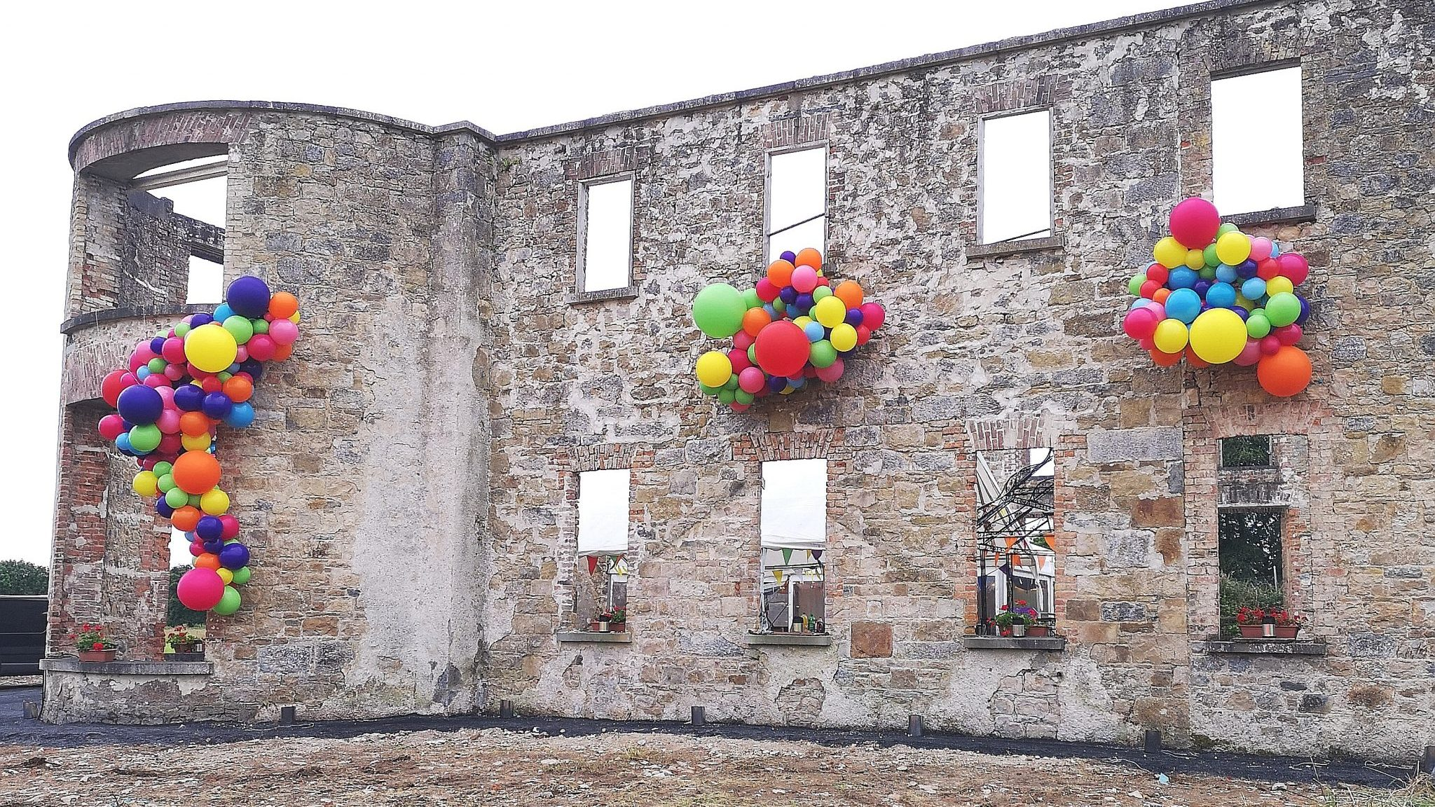 coloured balloons coming out old building windows