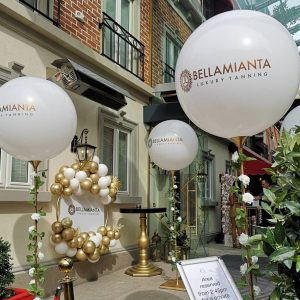 4 giant white balloons on poles and balloon hoop in gold