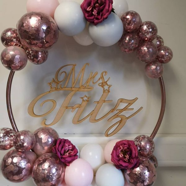 balloon hoop with rose gold wooden name insert and rose gold confetti balloons