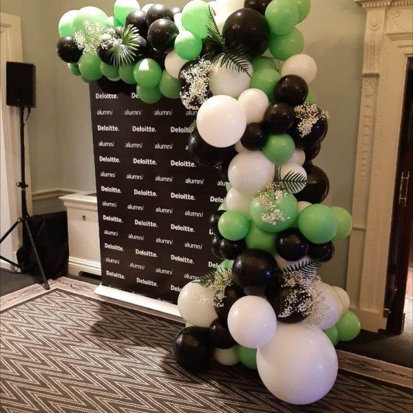 deloitte half balloon arch black green and white balloons