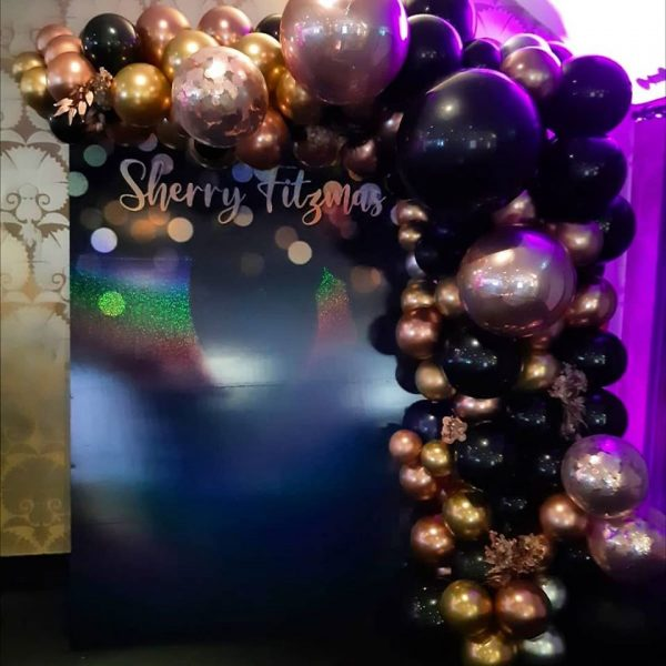half balloon arch black rose gold and gold balloons