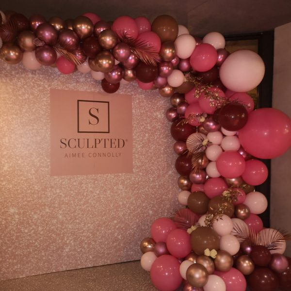 half balloon arch pinks and gold and flowers