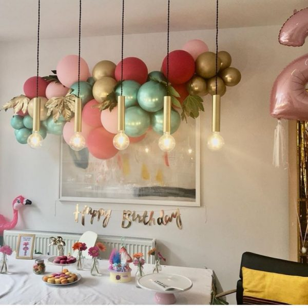balloon cluster hanging on wall in front of cake table