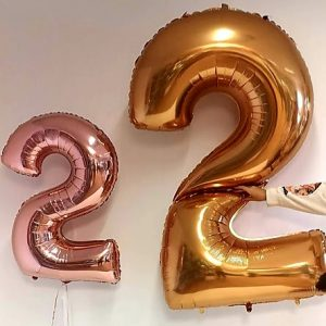 giant gold number 2 againest small rose gold number 2 balloon