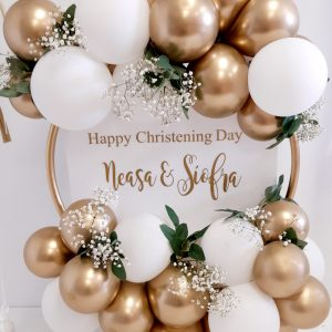 gold and white balloon hoop with greenery