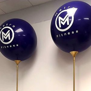 purple giant balloon with white text and mounted on gold pole close